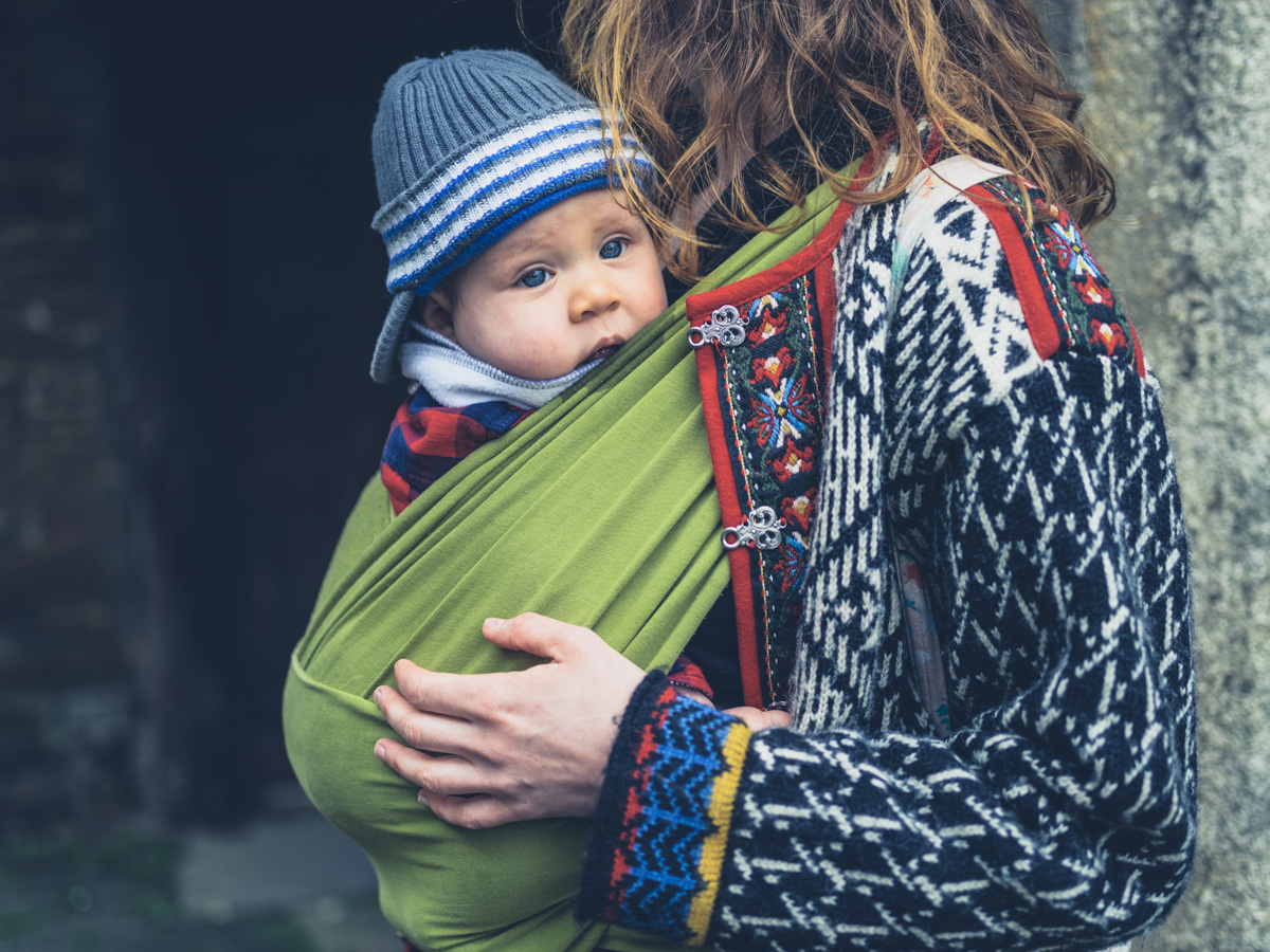 A young mother with her baby in a carrier sling is standing outside a historic building