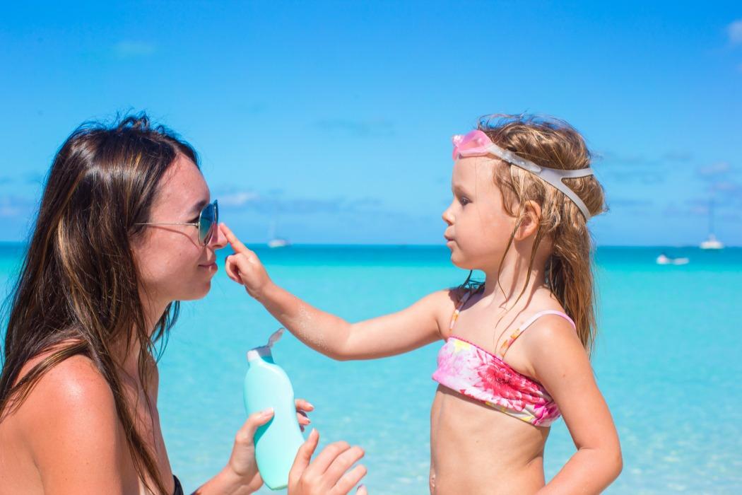 Child protection sun cream on the beach