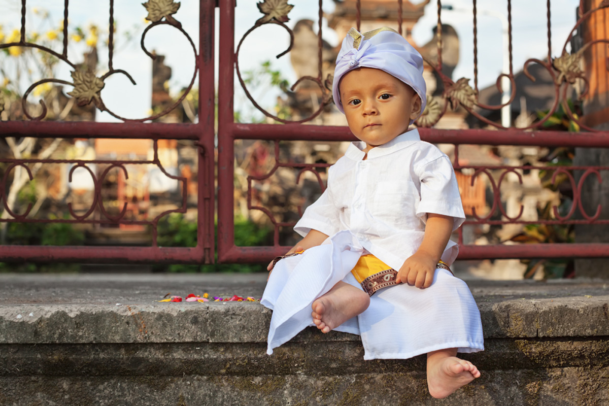 Portrait of balinese baby boy with smiling face in traditional costume Sarong sitting in hindu temple at religious ceremony. Bali island children lifestyle and national culture of Indonesian people.