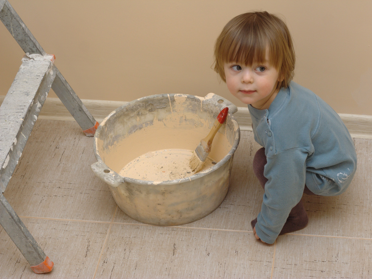 Little boy near the bucket with paintbrush