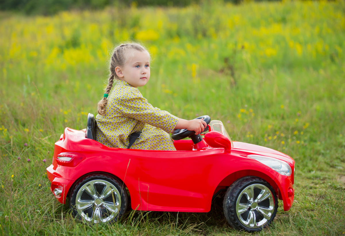 little girl riding a red car