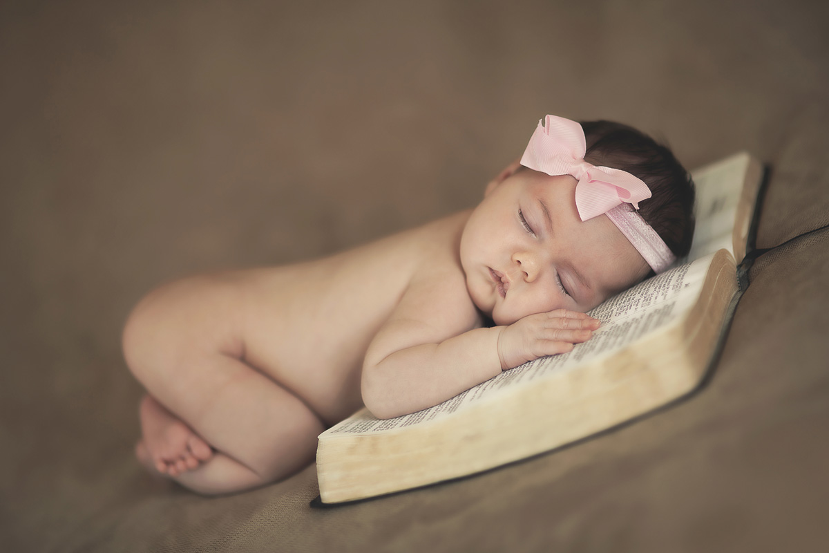 A baby sleeps on the pages of the Bible.