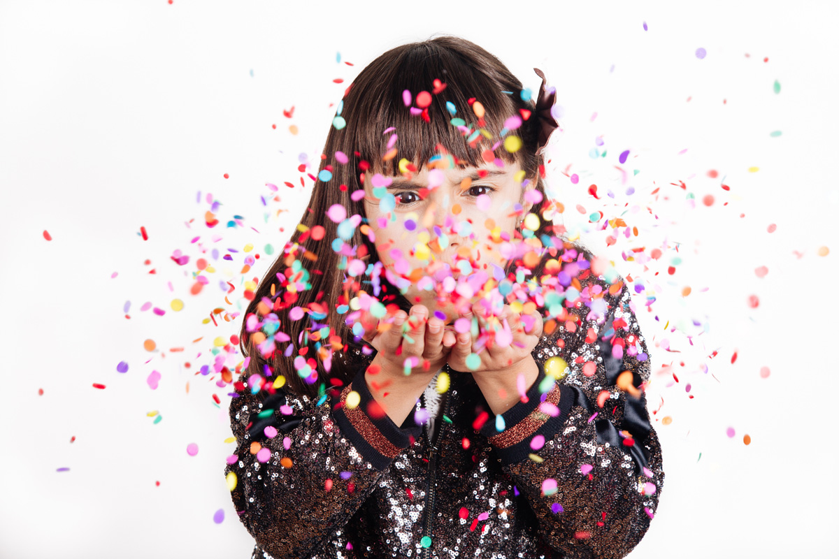 Funny little girl dressed for party in sequins blowing confetti . Isolated on white.