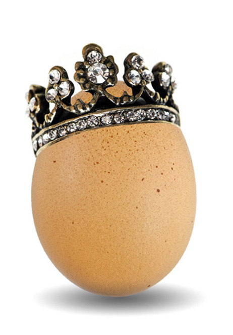brown natural egg with golden crown isolated on white background. easter decoration