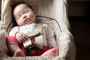 Infant fastened with seat belt for safety purpose in car seat